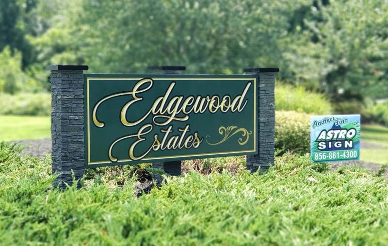 Edgewood Estates carved sign behind plants