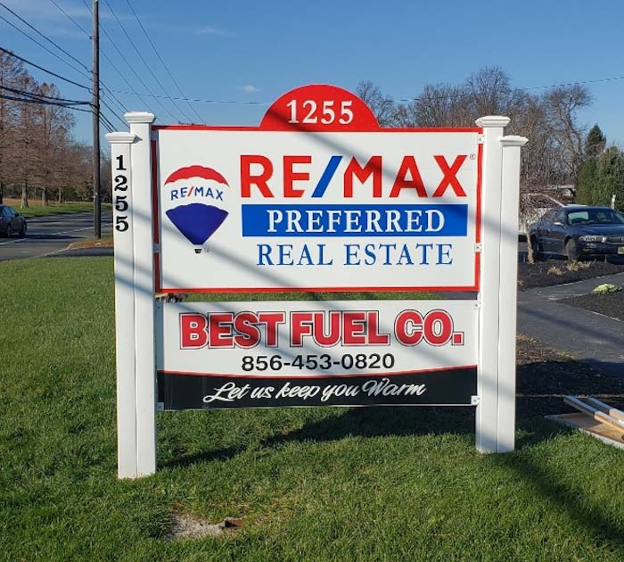 REMAX post and panel sign out in daylight on side of road