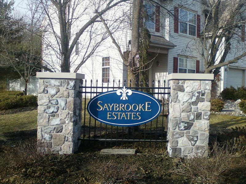 Saybrooke Estates carved sign hanging on black gate in daylight