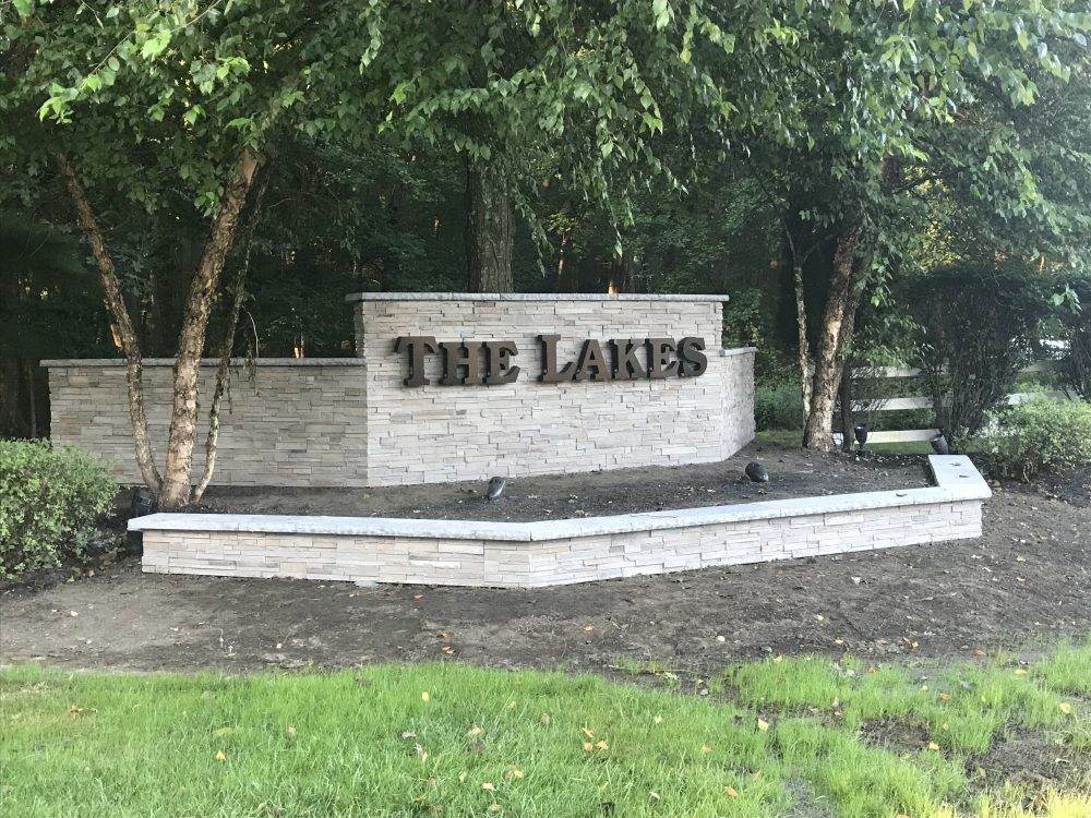 The Lakes sign on stone wall during daytime