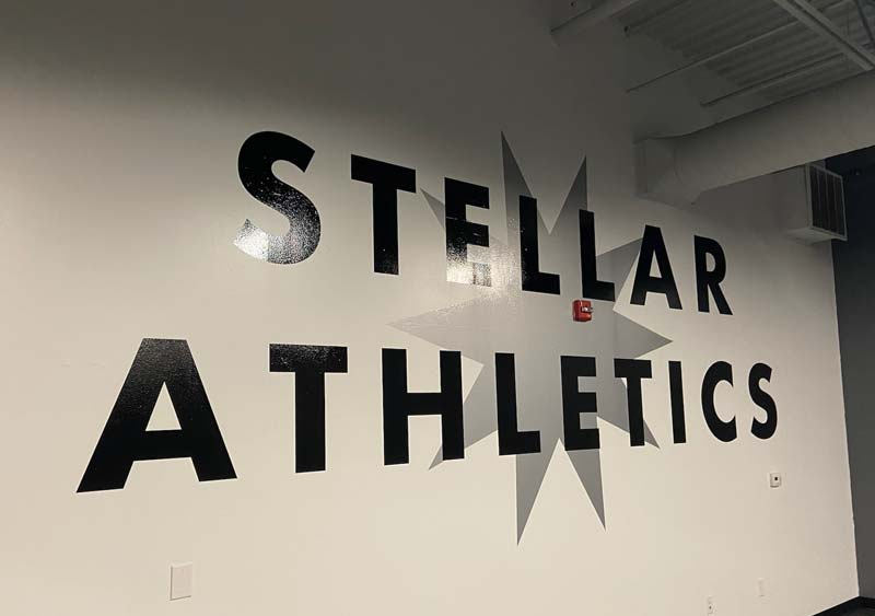 STELLAR ATHLETICS black letters on white wall interior signage