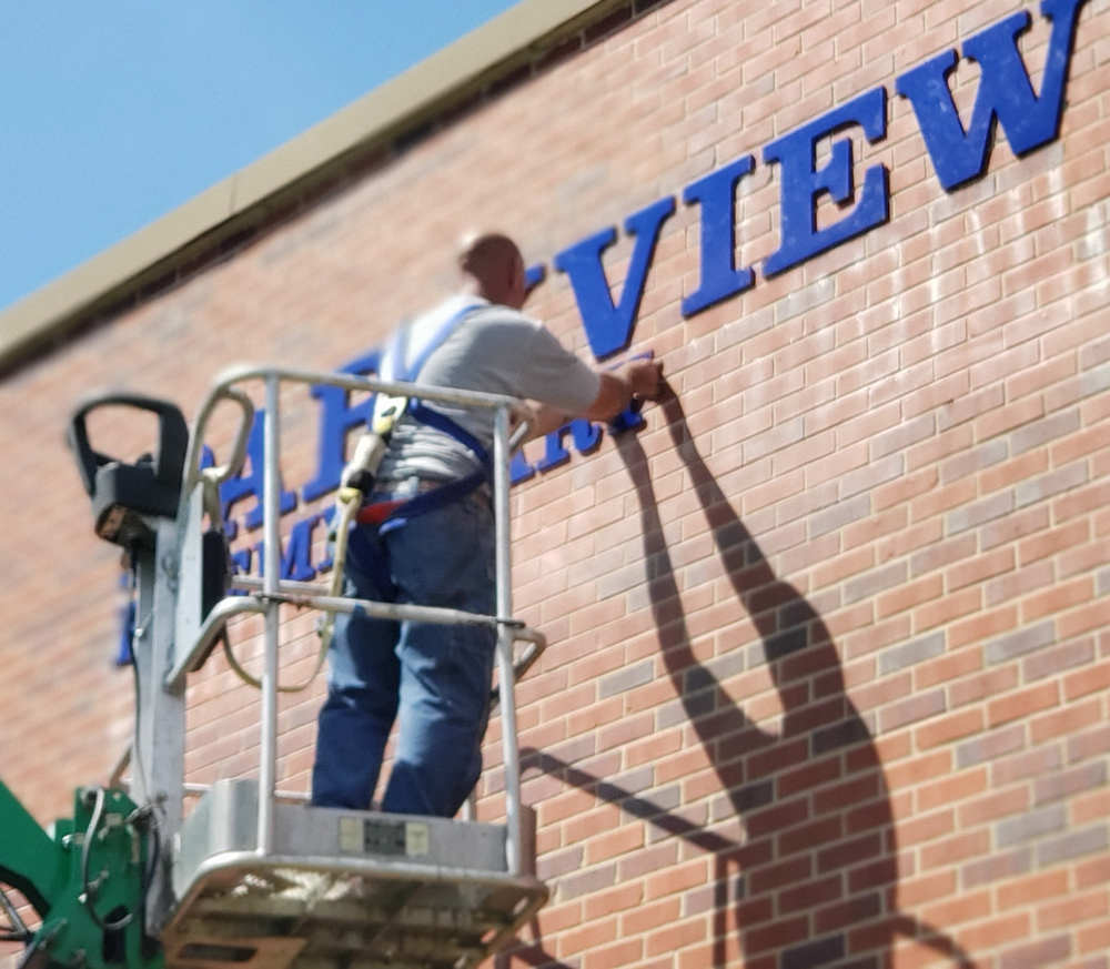 Man working on raised letter sign on brick wall
